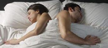 Una pareja duerme en la cama.