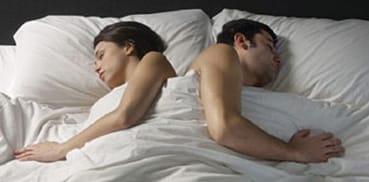 Una pareja duerme en una cama.