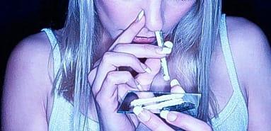 Una mujer esnifa una raya de cocaína.