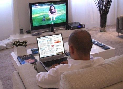 Una persona ve la tele a la vez que está conectado a Internet con un portátil.