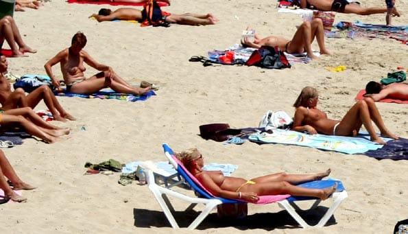 Jóvenes hacen topless para ponerse morenas.