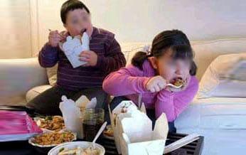 Niños obesos comen frente al televisor.