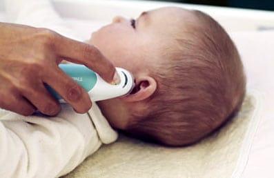 Comprueban con un termómetro si un bebé tiene fiebre.