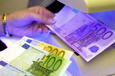Billetes de 500, 200 y 100 euros bajo la luz de una lámpara morada para comprobar su veracidad.