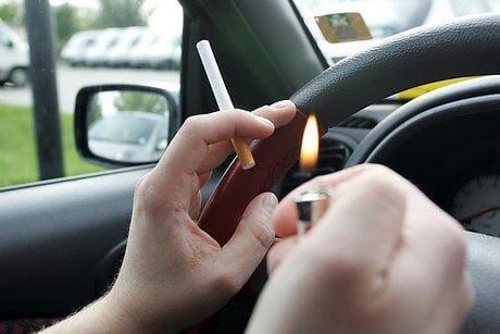 Un conductor se fuma un cigarro en su coche.
