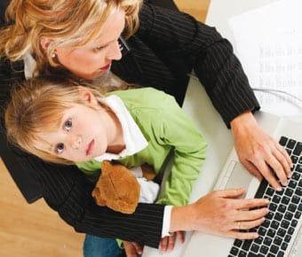 Mujer que teletrabaja atiende una llamada de teléfono mientras cuida de su hija.