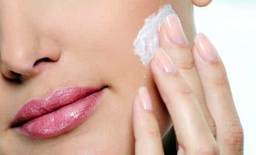 Una mujer se hidrata la piel de la cara con crema.