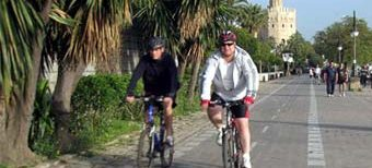 Dos ciclistas pasean en bici por Sevilla.