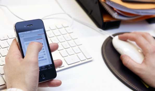 Un teletrabajador desde su puesto de trabajo en su casa maneja el iPhone y el ordenador.