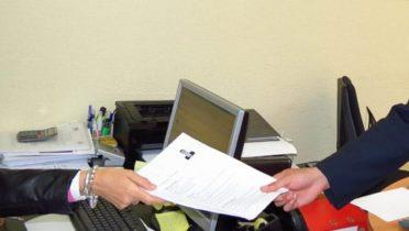Un trabajador entrega el currículo de un amigo recomendado para un puesto de trabajo.