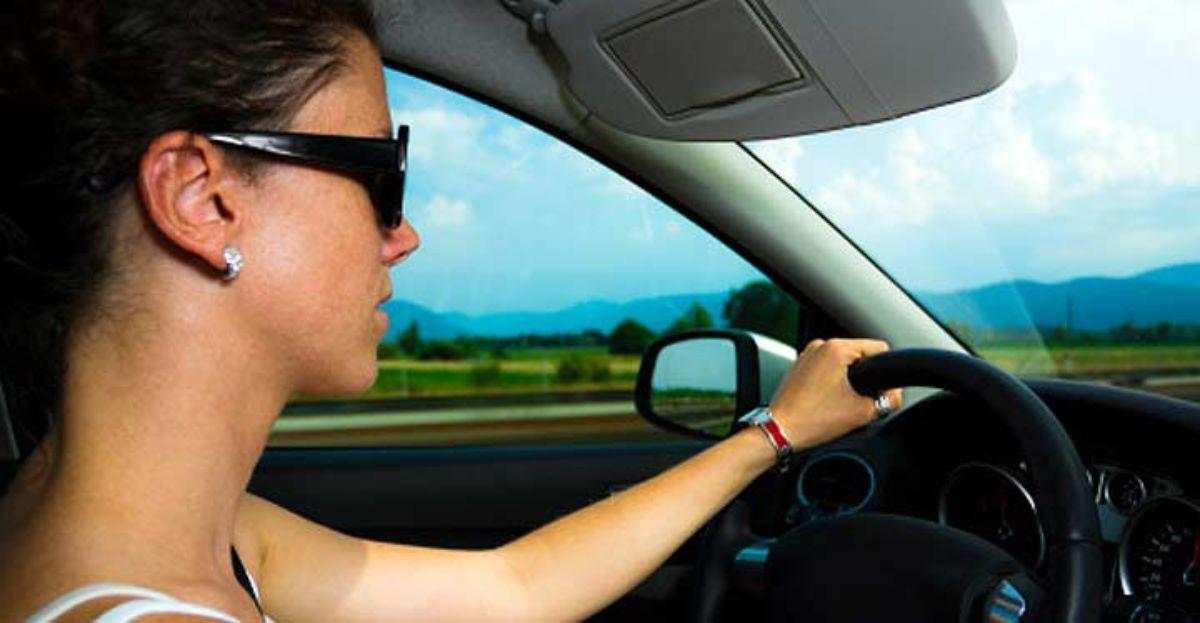 Una mujer conduce con gafas de sol.