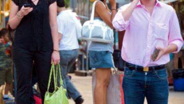 Gente en la calle usa el smartphone.