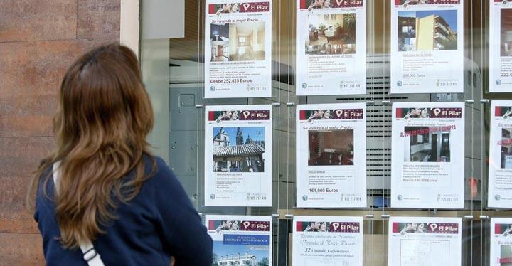 Mujer viendo ofertas en un escaparate de una inmobiliaria