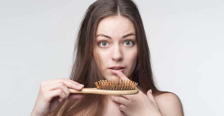 Mujer con cepillo del pelo que muestra la caída del cabello