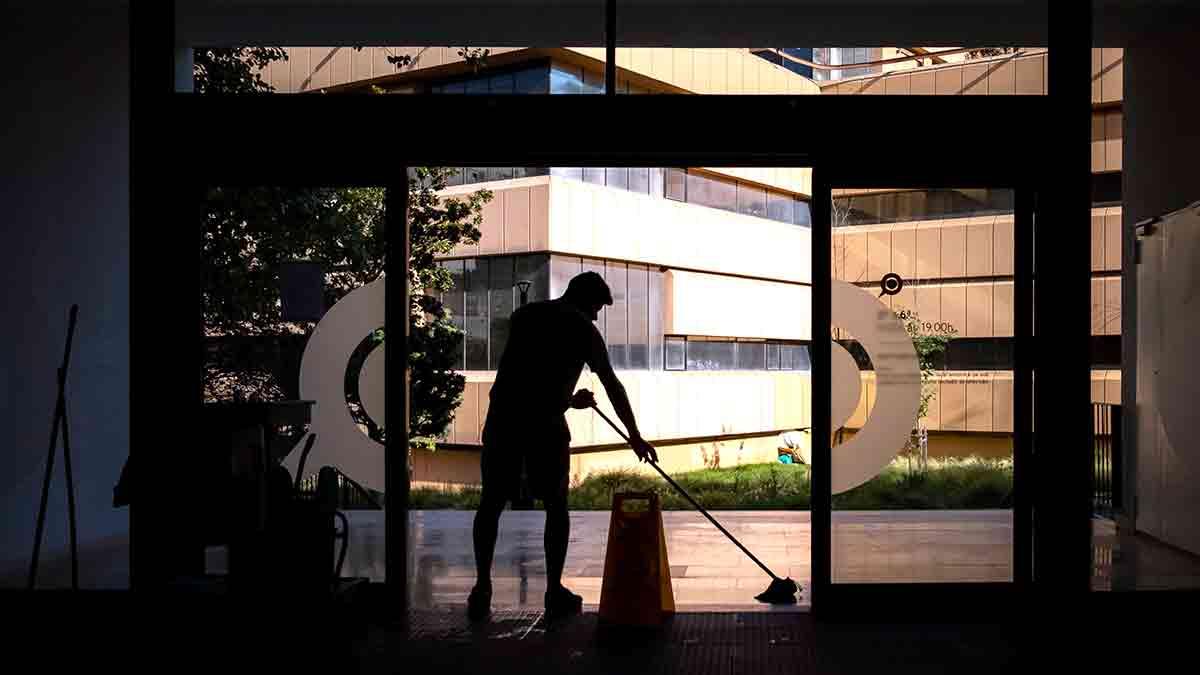 Empleado de la limpieza fregando un portal